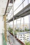 Andamio fijado en un rascacielos edificio construido del bloque de cemento grande en una urbanización foto de archivo libre de regalías