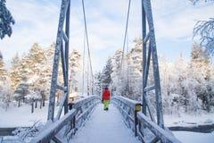 Andando a ponte sobre o rio da turfa de Rudanjoki no inverno imagem de stock