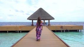 Andare femminile sul ponte sulla spiaggia con acqua trasparente dell'oceano in Maldive archivi video
