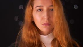 Andas ser den caucasian ljust rödbrun kvinnlign för närbilden med den koncentrerade framsidan och exakt på kameran i stillhet, ko lager videofilmer