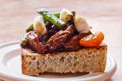 Andconfit på det grillade brödet Vit plattabakgrund Royaltyfria Bilder