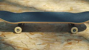 Ande en monopatín con las ruedas blancas en un fondo de madera en un skatepark almacen de video