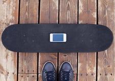 Ande en monopatín con smartphone y las zapatillas de deporte de la pantalla sobre el fondo de madera texturizado, endecha del pla Fotografía de archivo libre de regalías