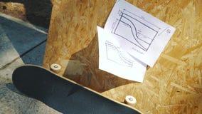 Ande en monopatín en un fondo de madera con los planes para un miniramp en un skatepark metrajes