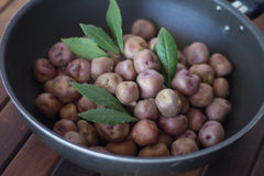 Andean potatoes in a pan. Over a wooden table Royalty Free Stock Photography
