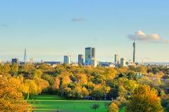 Andedräkt-ta den panorama- sceniska sikten av London cityscape som ses från den härliga primulakullen i St-regenter, parkera Royaltyfri Fotografi