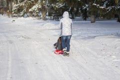 Andere het lopen op een lege, sneeuwstraat die moderne slee drijven Stock Afbeelding