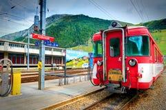 ANDERMATT,瑞士, 2010年8月, 19日:火车站和Bernina冰川明确山训练高山红色的旅客长途汽车 免版税库存图片