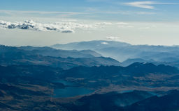 Andes. The Andes Mountainrange just east of Lima. Picture taken from an aircraft. Andes, mountains, Peru, Lima, haze, sky, lake, clouds royalty free stock photo