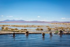 Andes, Bolivia - Oct 11th 2017 - Group of tourists enjoying a hot bath at a natural spring in the Andes Altiplano, blue sky, exoti royalty free stock photography