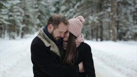 Andkissing молодых привлекательных пар идя в лесе зимы под сильным снегопадом движение медленное сток-видео
