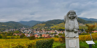 Andlau, Alsace village, vineyard, statue of monk carrying wine barrel Royalty Free Stock Image
