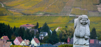 Andlau, Alsace village, vineyard, statue of monk carrying wine barrel Stock Image