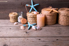 Сandle and coastal  items on  aged wooden background. Royalty Free Stock Photography