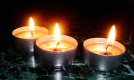 Сandles. Fire in candle from dark Royalty Free Stock Photography
