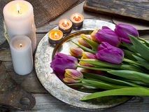 Ð¡andles and tulips on rustic wooden background. Top view royalty free stock photo