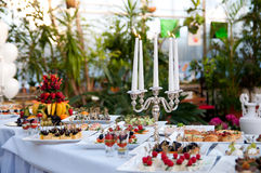Сandlestick and table with luxury food. Banquet Royalty Free Stock Images