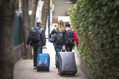 Tourists travelers carrying suitcases in hand walking Royalty Free Stock Image
