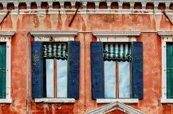 Andra golv av den gamla röda husfasaden med trämörkt - blåa fönster fotografering för bildbyråer