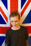 Androgyne girl looking dawn in front of Union Jack Flag Stock Images