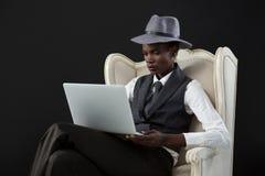 Androgynous mężczyzna używa laptop podczas gdy siedzący na krześle Obrazy Stock