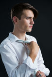 Androgynous man adjusting his tie. Against black background Royalty Free Stock Image