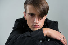 Androgynous man in black shirt posing against grey background. Portrait of androgynous man in black shirt posing against grey background Royalty Free Stock Image