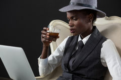 Androgynous man drinking whiskey while sitting on a chair. Against grey background Stock Photo