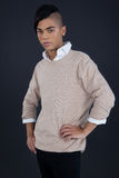 Androgynous man posing with hands on hip. Against grey background Royalty Free Stock Photos