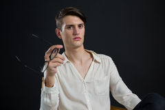 Androgynous man posing while holding spectacles Stock Photo