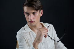 Androgynous man posing while holding spectacles Royalty Free Stock Images