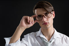 Androgynous man posing in spectacles. Against black background Stock Images