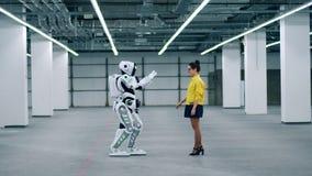 Android dotyka dziewczyny rękę, stoi w pokoju wpólnie zdjęcie wideo