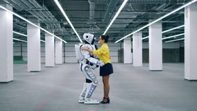 Android and a girl hug, greeting each other and talking. stock footage
