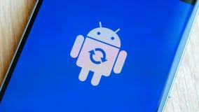 Android-het pictogram van het robotembleem op het slimme de telefoonscherm van Samsung tijdens update stock footage