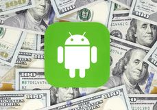 Android icon printed on paper, cut and placed on money background stock images