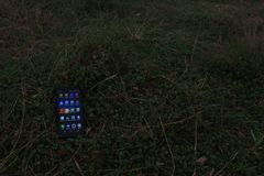 Android phone and social media. Android phone power on lay on the grass as if it lost , suitable for illustrating lost and recovered moble royalty free stock photos