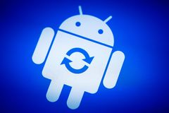 Android robot logo icon on the smart phone screen during update installation Stock Photo