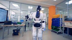 Android rusza się swój ciało i ręki podczas gdy stojący w konstruuje lab zbiory wideo