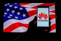 Android-Smartphone que muestra el logotipo de Huawei delante de la bandera de los E.E.U.U. imágenes de archivo libres de regalías