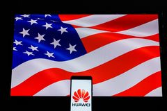 An android-smartphone that shows the Huawei logo in front of the USA flag. PERAK, MALAYSIA - MAY 24, 2019: An android-smartphone that shows the Huawei logo in royalty free stock image
