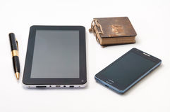 Android tablet and phone and old antique paper notebook with black pen.  stock photography