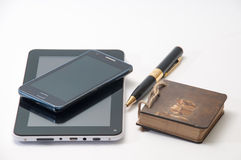 Android tablet and phone and old antique paper notebook with black pen.  stock photo