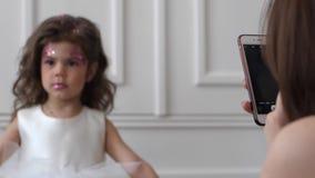 Android w kobiety ` s rękach robi obrazkowi mała dziewczynka w biel suknię indoors zbiory