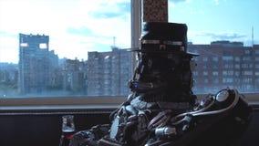 Androide del metal que se sienta en la tabla en restaurante con la copa de vino en el fondo de la vista de edificios altos de la  fotos de archivo