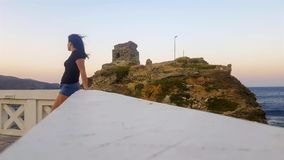Andros island in Cyclades in Greece with a woman relaxing against the town castle.  stock video footage