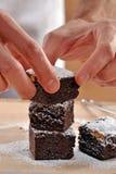 Ands που προετοιμάζει και που τεμαχίζει τα φρέσκα brownies Στοκ Εικόνα