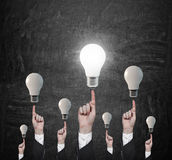 Ands pointing on lightbulbs Royalty Free Stock Photography