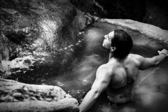 Нandsome guy with long hair and piercings on waterfalls in a rain forest against a background of clear blue and green water. Tarzan concept. Black and white Royalty Free Stock Image