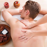 Andsome man relaxed and enjoying back massage. Stock Photo